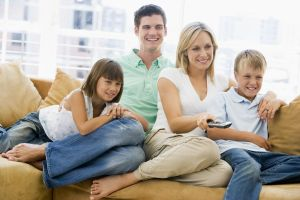 Families Sitting In Living Room With Remote Control Smiling