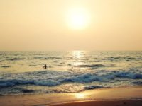 Tourists enjoy the sea on sunset - vintage filter. Tropical beach and peaceful ocean - vintage filter. Sunset on the Beach in Varkala Kerala India. Wide slider photo.