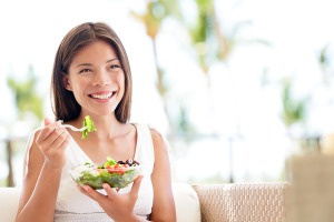 Healthy lifestyle woman eating salad smiling happy outdoors on b